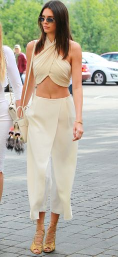 Wheretoget - White halter crop top with a white shoulder bag, white flowy pants,  and sunglasses