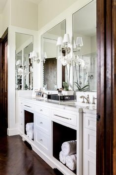Exquisite master bathroom features a white double washstand fitted with open bins lined with rolled up towels topped with white beveled marble surrounded by four framed mirrors illuminated by Robert Abbey One Light Crystal Wall Sconces alongside a dark stained wood herringbone floor.
