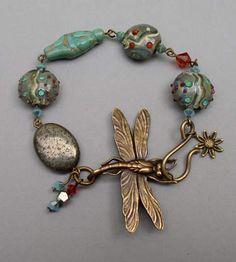 Dragonfly Goddess Bracelet  A large, finely detailed antiqued brass dragonfly completes a circle of hematite, handmade lampwork beads, Swarovski crystals and a antiqued turquoise Czech glass goddess bead.