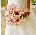 The bridesmaids will have clutch bouquets of pale pink peonies, ivory garden roses, pale pink dendrobium orchids, ivory spray roses, and white cymbidium orchids with pink centers wrapped in charcoal grey ribbon.