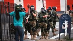 Militarized police raise their weapons at a peaceful citizen as they stray from one of their unlawful blockades in Ferguson, Missouri.