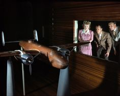 """October 1942. Experimental staff at the North American Aviation plant in Ingle- wood, Calif., observing wind tunnel tests on a model of the B-25 (""""Billy Mitchell"""") bomber. 4×5 Kodachrome transparency by Alfred Palmer."""