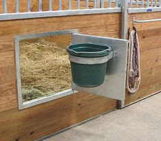 A swing out grain dish allows staff to grain from the aisle without going in the stall, reducing risk and facilitating feeding to save time. Barn Stalls, Horse Stalls, Horse Barn Plans, Horse Barn Decor, Horse Stall Decorations, Horse Tack Rooms, Horse Barn Designs, Horse Shelter, Goat Shelter