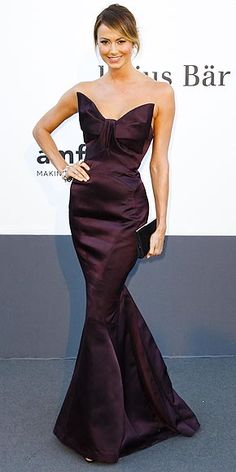 Stacy Kiebler forgoes her go-to short hemline for an eggplant Zac Posen gown with a large bow bodice and fishtail bottom, which she accessorizes with a black clutch and tons of bangles at Cannes 2013