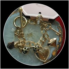 Juicy Couture Beautiful Charm Bracelet !   Gorgeous 7 inch Juicy Couture Charm Bracelet ! Toggle clasp ! 5 charms plus a little bead by clasp ! The sunglasses and heart are 2 sided ! One side gold with black hearts ! Other side of sunglasses is pink ! Other side of heart is gold with Juicy written on it plus key hole and tiny rhinestones ! Really precious !  Juicy Couture Jewelry Bracelets