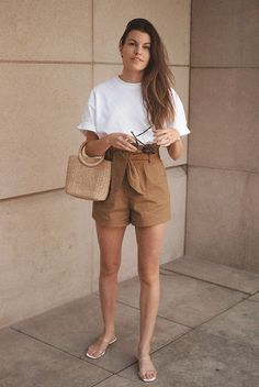 Fashion blogger Un-Fancy wearing a white ruffle sleeve tee, brown paperbag shorts, clear sandals and a straw bag. Summer outfit, vacation outfit, casual outfit, beach outfit, summer style, summer vacation outfit, summer fashion trends 2019, comfy outfit, travel outfit, neutral outfit, minimal outfit, minimalism, #fashion2019 #summerstyle #vacationstyle #casualstyle #summertrends2019 #neutrals #neutralstyle #minimalism #minimalstyle