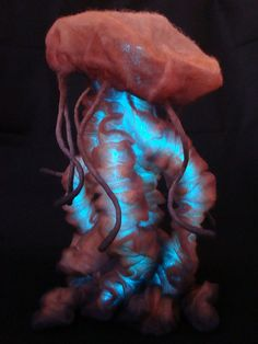 "This is my nuno felted JellyFish. He stands about 18"" tall.    Wet felted with 100% wool, then needle felted over a wire armature. He was then airbrushed with fabric & acrylic paints.    He also has glowing ""El Wire"" inside his tentacles. In the dark it glows bright blue and can be seen through the very thin layers of felt.    christine prusha"