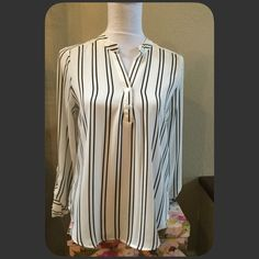 "Black and White Striped Hi-Lo Blouse Cute striped chiffon style hi-lo blouse. Great with jeans, slacks, skirts. Wear casual or to the office to an evening out. Sleeves have a button to wear a little up or wear down. Be cute tucked in as well with a pencil skirt. Measures approximately 24.5"" front, back 28.5"", sleeves 25"" unbuttoned. Material 100% Polyester. NWT. Size Medium. Mine Tops Blouses"