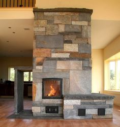 Masonry Heater with wrap around heated bench, direct fire oven (on kitchen side), and wood storage by Carsten Homstead of Massachusetts. homespunworks.com