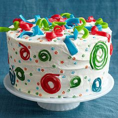 Cute use of Airheads: as colored streamers on top of a cake. Slice them, then twist them around your finger. I think in general this cake is a bit busy; I'd keep the sides all white and skip the licorice/star confetti, but I love the airhead twists.