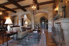 The living room has hardwood floors, a wood-burning fireplace, decorative lighting and stone arches.