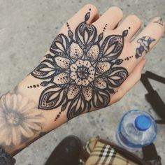 Black ornamental mandala tattoo on the left hand