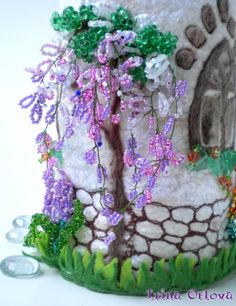 beaded wisteria climb along the side of the house.  Stitchery forms the 'stone's on the walls of the house.