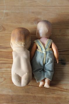 "two vintage dolls from the 40s. one has limbs and is made of hard plastic. he's dressed in a corduroy suit with eyes that open when he sits. the other doll is rubber and made in japan. it has a startled look and bright red lips. the back reads: ""FirstMaid Baby Japan"". Shop: Rachael"