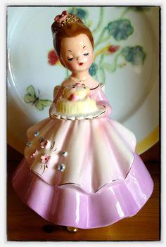 A Josef Originals girl holding a cake. `