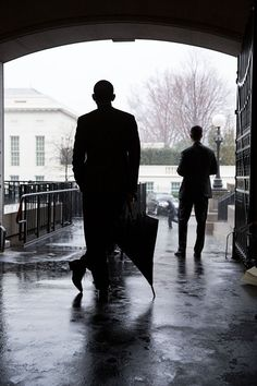 President Obama waits for a heavy rain to pass before crossing West Executive Avenue from the Eisenhower Executive Office Building to the West Wing of the White House, March 12, 2013.