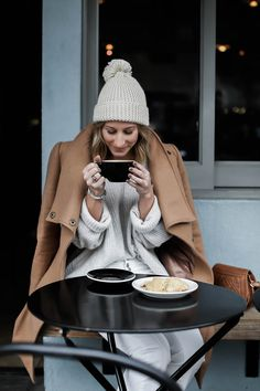 winter white outfit with pom pom beanie and camel coat, light gray sweater