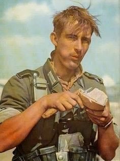 A German soldier eating bread. -