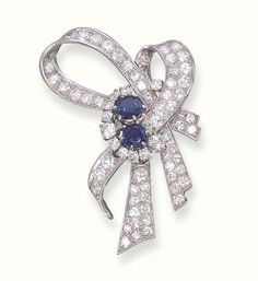 A SAPPHIRE AND DIAMOND BROOCH   Designed as a diamond-set ribbon gathered by two circular-cut sapphires within a circular-cut diamond crescent, with French assay marks for platinum