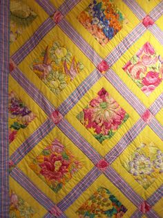 Yellow Kaffe Fassett quilt from the 2010 Festival of Quilts show (UK).  Contrasting striped periwinkle-and-pink sashing; pink and green floral blocks.  Photo by Claire Leggett