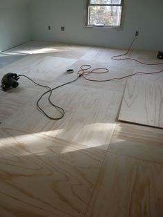 The walls upstairs have been painted a light green, Sherwin Williams' Opaline. And now Chad and Scott are putting down 4X4 sheets of pine plywood. This is going to be our floor for the time b…