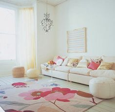 """""""A escolha de cores foi totalmente baseada no tapete, o elemento focal do espaço. A luminária enfatiza o toque romântico da sala, assim como as almofadas em rosa e a cortina vaporosa. A mesa de apoio, bem pequena e os puffs se apresentam dispostos de forma a não esconder o lindo padrão do tapete. O quadro, simples e de cores claras, não briga para chamar a atenção."""" (comentários de Rosana Silva)"""