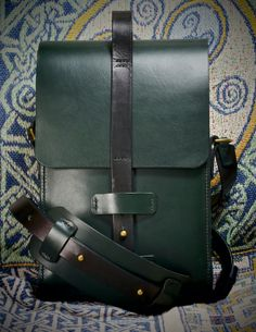 Modern, clean lines, with traditional, hand-crafted style. The Kline Leather Satchel is a unique piece that will see you standing out from the crowd. Large enough to take an iPad, but not so large that it hinders movement or encourages clutter. This is the bag for the sleek tech.  Hand-crafted from Dark Racing Green, 3mm thick, vegetable tanned leather, this leather satchel will take the stress of every day use with ease. You will be amazed how comfortable it is to carry, and how well it…