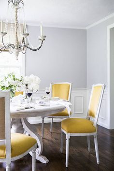 Pale blue gray dining room with yellow upholstered chairs