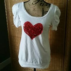 Adorable white top with sequined red heart This cute fitted top has a scoop neck, banned bottom and flattering sleeves to make you look great. Pretty  Tops Tees - Short Sleeve