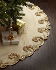 "Handcrafted Christmas tree skirt. Plastic and glass beads on cotton/Lurex fabric. 64""Dia. Spot clean. Imported."