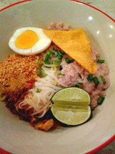 Bangkok, Thailand street food: Dry stick noodle with minced pork and duck egg. With spicy tom yum and peanut mix.
