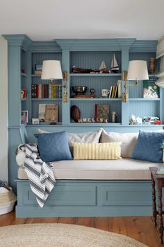 Playful blue makes a small reading corner feel like its own roomy space. This trim is painted Van Courtland Blue by Benjamin Moore.