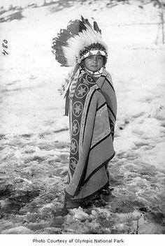 Native American child wearing a headdress and blanket, possibly on the Olympic…