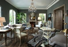 This formal living room with its zebra rug and crystal chandelier appeals with its modern decor mixed with traditional furnishings.