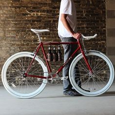 Bicycles: a classic burgundy red fixie bike with a white saddle, handlebars and tyres.