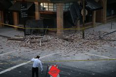 NAPA, CA - AUGUST 24:  A reporter surveys the scene of a building collapse following a reported 6.0