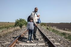 Syrian refugees, Hassan, 35, and his daughter Tasneem, 5, stand on train tracks in Hungary after crossing the border with Serbia on September 3, 2015.