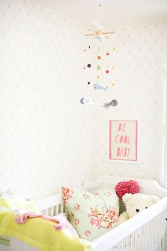 """White nursery with yellow blanket, pink pillow, """"Be Cool Baby"""" art, and mobile"""