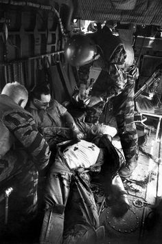 """""""Farley opens a first-aid kit to apply to Magel's wound as Hoilien watches Owens, the wounded gunner (with dark glasses), slumped in the rear."""" Larry Burrows Vietnam"""