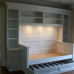 This is a neat way to conserve space in a small room!  A trundle bed with tons of space for books and other things.