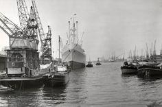 Havens. Links Hijskranen op de voorgrond kleinere vrachtschepen aan de kade, groter schip met sleepboten in de flank rechts ook kleinere vrachtschepen en op de achtergrond veel hijskranen. Haven (w) van Amsterdam, Nederland, mei 1957.