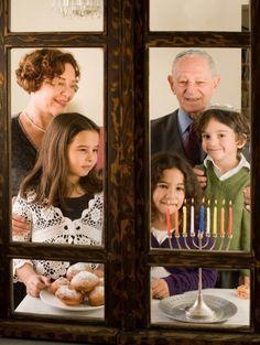 A Jewish family lights the Chanukah menorah.