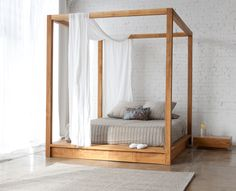 Light wooden canopy bed creates an airy spacious bedroom