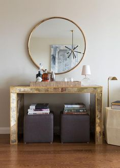 Chic living room boasts a Wisteria Gilt Minimalist Mirror placed above a gold antiqued mirrored console table, Worlds Away Madison G Console Table, topped with a raffia tray filled with libations.