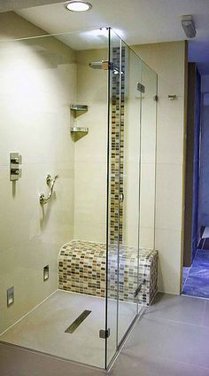 A frameless glass shower enclosure with ultra low profile shower tray and tiled…