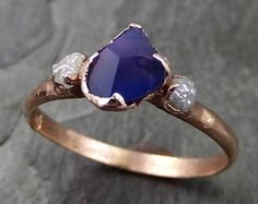 Raw rough and partially faceted by my husband violet sapphire with raw conflict free diamonds on each side. I hand carved this ring in wax and cast it in recycled solid 14k gold using the lost wax casting process. This one of a kind raw gemstone ring is a size 9 1/2 it can be resized. The sapphire stone measures about 8.5mm X 7mm . The rough diamonds are about 3mm. Throughout all time and history, in every tribe and culture all around the world crystals minerals and gemstones have used ...