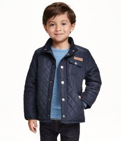 Lightly padded, quilted jacket with a corduroy-lined stand-up collar and snap fasteners at front. Side pockets, chest pocket with flap and snap fastener, corduroy elbow patches, and snap fastener at cuffs. Fleece lining.