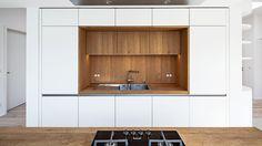 Küche mit den abgerundeten Radien an den vorderen Kanten der Kücheninsel. Die Fronten wurden seidenmatt weiß lackiert, die Nische aus Eichenfurnier gibt durch die indirekte Beleuchtung ihren warmen Ton in den Raum davor ab.