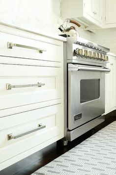 Heidi Piron Design and Cabinetry: Kitchen features white inset cabinets with modern polished nickel knobs and pulls. ...