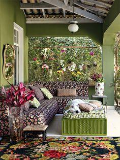 Flores também cobrem o sofá (produzido pela Tapeçaria Monelli com tecido da Fernando Maluhy) e os acessórios, um acervo pessoal que migra pela casa. No vaso alto, folhas vermelhas de cordiline.